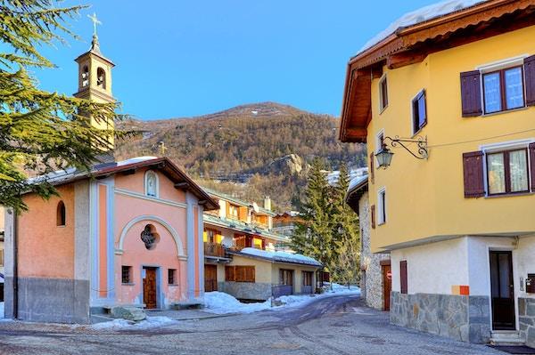 Liten torg omgitt av typiske hus og kapell i det populære turistskistedet Limone Piemonte i Italia.