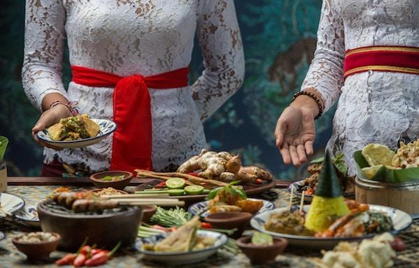 Indonesisk mat - Mange tradisjonelle balinesiske retter på bordet. Kvinner serverer.