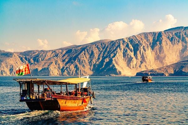 Båttur i Omanbukten med fjell i bakgrunnen.
