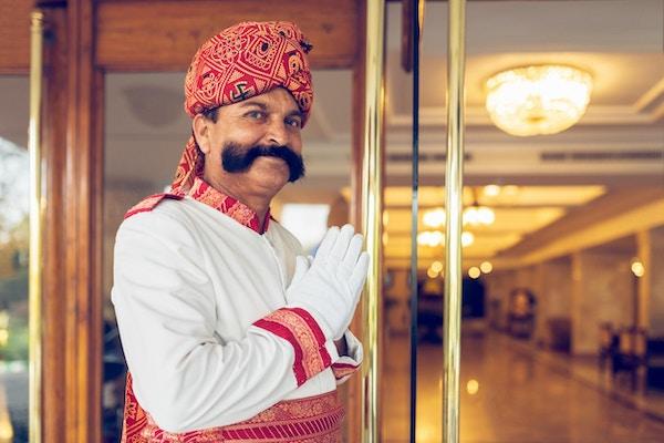 Indisk portner som ønsker gjester velkommen ved en hotellinngang i Agra, India