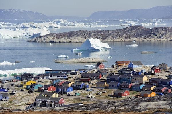 Utsikt over byen Illulisat med hus og isbreer, Grønland.