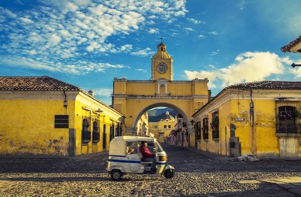 en tuk-tuk-taxi passerer foran Santa Catalina-buen i Antigua, Guatemala.
