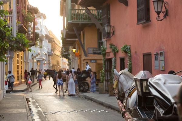 Cartagena, Colombia. En turistdestinasjon, gamlebyen ligger på innsiden av murer som opprinnelig ble laget for å beskytte byen fra piratangrep. Gatene på bildet er laget av brostein og fulle av fotgjengere. Hest og vogn er en populær måte for turistene å se byen på.
