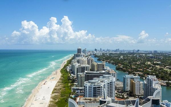 South Beach i Miami. Full utsikt over stranden til venstre og byen til høyre. Vakker blå himmel på en klar dag.