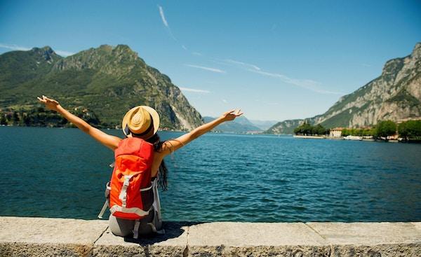 Kvinne på reisefot ved innsjø.