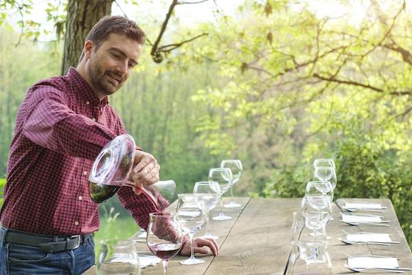 Vinsmaker og vinglass på et trebord utendørs på landsbygda