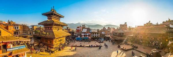 Varmt solnedgangslys som fyller de travle brosteinene på Taumadhi-plassen, oversett av de gamle templene i Bhaktapur, UNESCOs verdensarvliste i Kathmandu, Nepal.