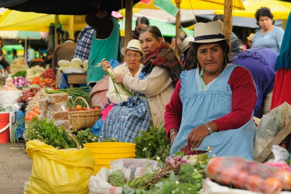 Ecuadorianske etniske kvinner i nasjonale klær som selger landbruksprodukter og andre matvarer på et marked i Gualaceo-landsbyen