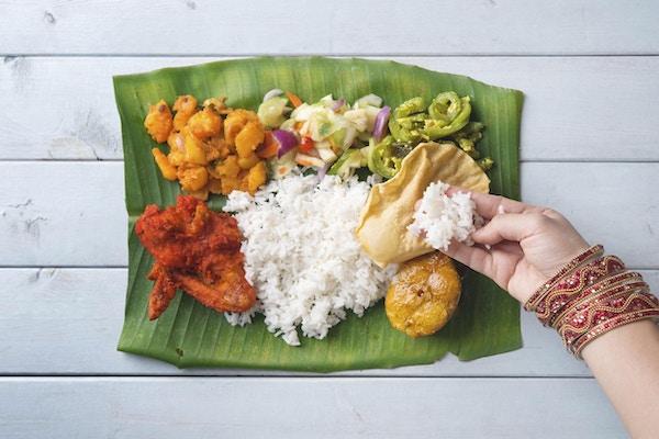 Indisk kvinne spiser bananblad ris. utsikt over hodet på trespisebord.