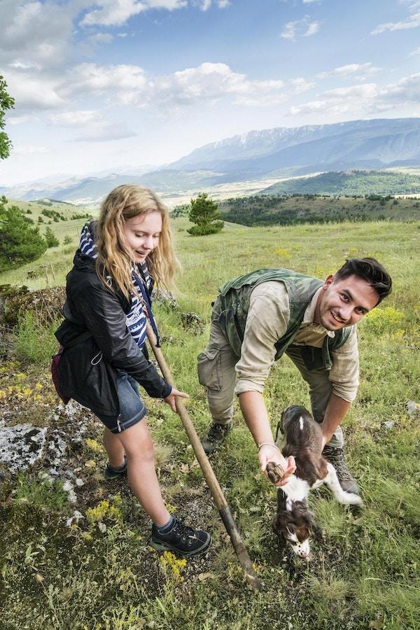 Blond tenåringsjente bruker vanghellaverktøyet for å hjelpe Springer Spaniel-hunden med å grave frem trøfler slik den mannlige jegeren i 20-årene gjør på en sommerdag, Abruzzo, Italia, Europa