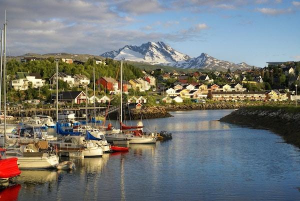 Utsikt over småby ved foten av et fjell med havn i forgrunnen, Foto.