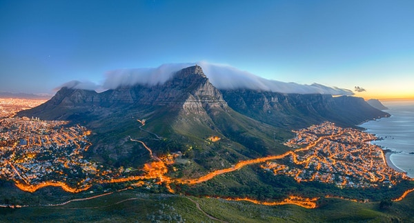 Table Mountain dekket av sitt typiske skylag og De Tolv Apostles. Nedenfor på venstre side kan man se Cape Town og den vakre Campsbukten på høyre side. Bildet er tatt rett etter solnedgang.
