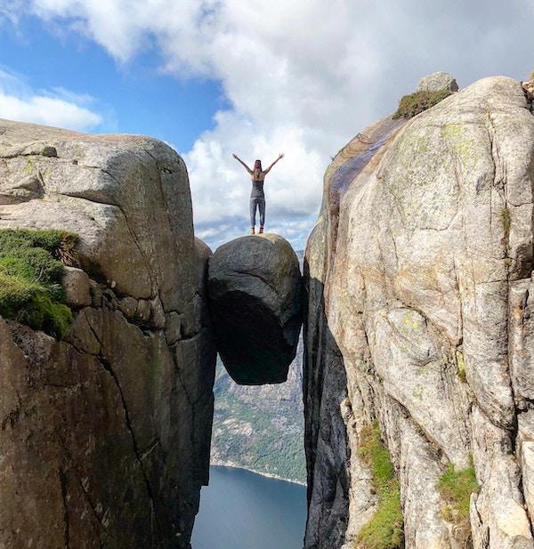 Kvinne som står på kjeragbolten fjellkant på Fjord i Norge sommeren 2018