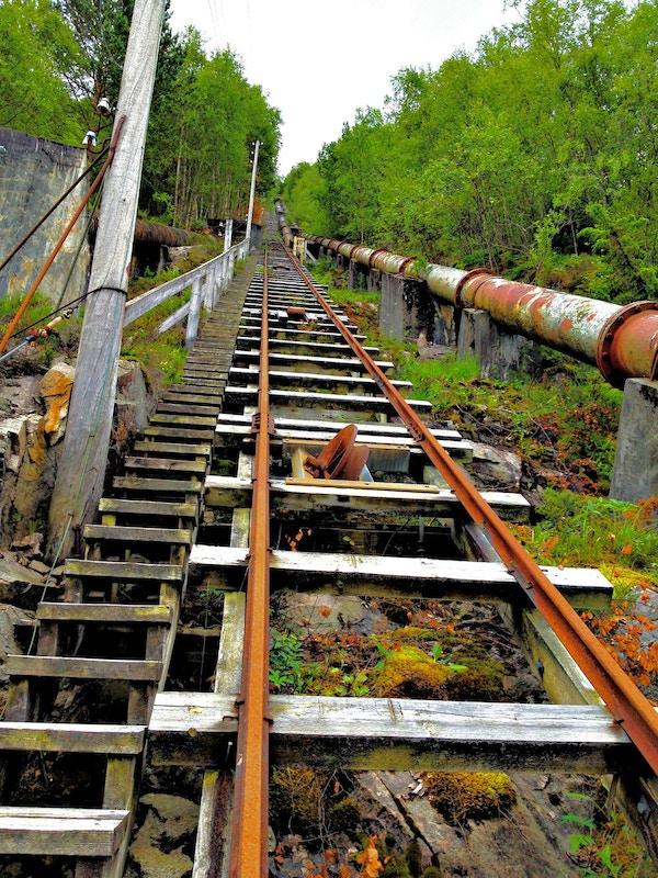 Tretrapp med togskinner og rørledning. Foto