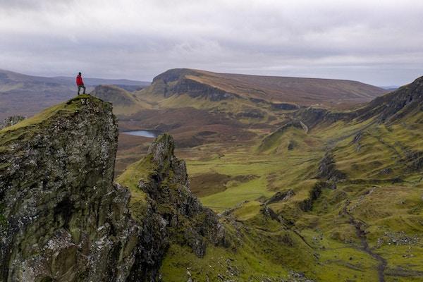 Grønt fjellandskap med menneske på en av toppene. Foto