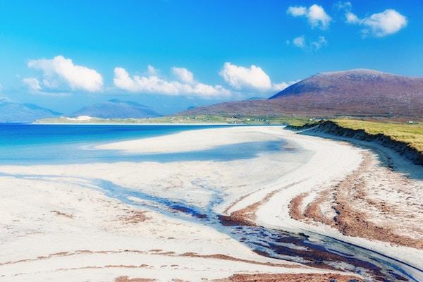Hvit sandstrand med goldt fjell i bakgrunnen. Foto