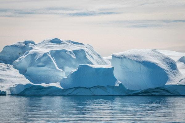 Et stort isfjell som ligger på rolig sjø i solen utenfor Ilulissat