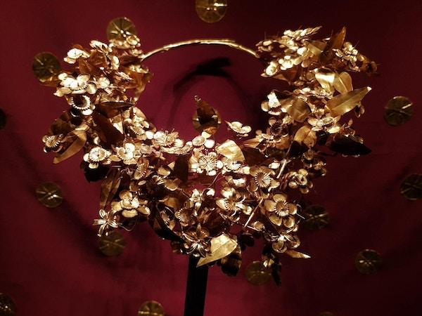 Detaljrikt gullsmykke på rød bakgrunn. Foto