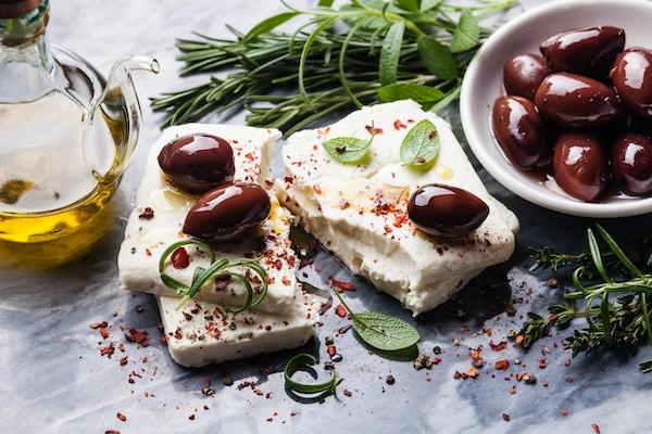 Fetaost med oliven og grønne urter på grå marmorbakgrunn