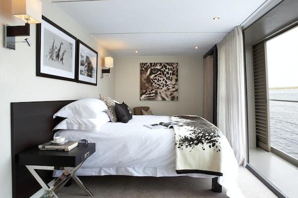 Lugar med dobbeltseng, nattbord, tepper, puter, bilder på veggene og stort vindu. Foto.