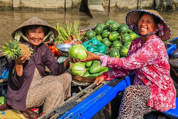Vietnamesisk kvinne som selger frukt på det flytende markedet, Mekong River Delta, Vietnam