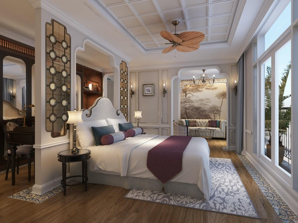 Lugar med tregulv, dobbeltseng, møbler, tepper, puter, takvifte og stort vindu. Foto.