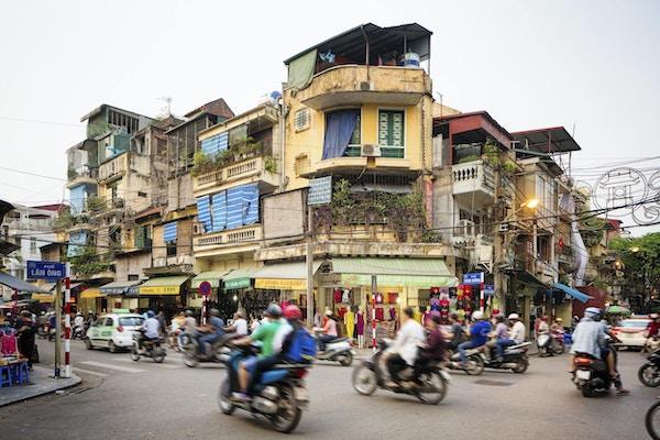 Opptatt gatehjørne i gamlebyen i Hanoi, Vietnam. Mange mennesker pendler på motorsykler eller biler. Gaten er omgitt av butikker og leilighetsbygg.