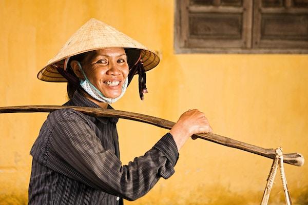 Smilende kvinne som bærer frukt med gult bygg i bakgrunnen. Foto.