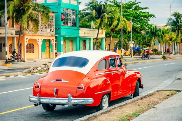 Rød amerikansk parkeringsplass ved en gate i Cienfuegos, Cuba