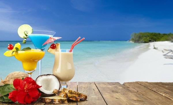 Pina colada, fersken daiquiri og blå curaçao cocktailer på et trebord med tropisk strandbakgrunn. Disse drinkene tilbys mest på tropiske feriedestinasjoner. Ved bunnen av glassene er en halv og en hel kokosnøtt, tre skiver ananas og en rød hibiskusblomst. Forgrunnskomposisjonen er til venstre for rammen og etterlater et nyttig kopierom midt til høyre.