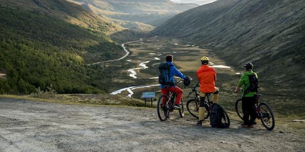 Syklister som ser på soloppgangen i Grimsdalen.