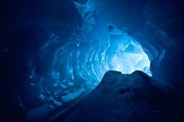 blå ishule dekket med snø og oversvømmet av lys