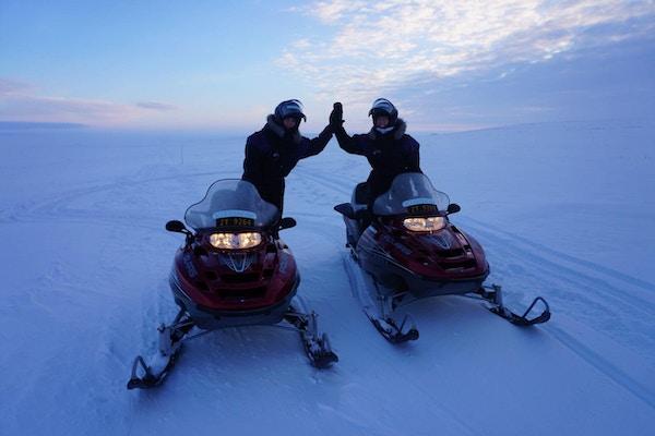 To personer kjører hver sin snøskuter i solnedgang