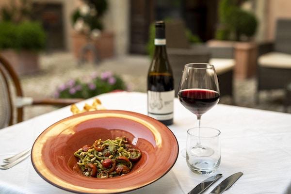 en rød tallerken med mat og et glass rødvin til siden