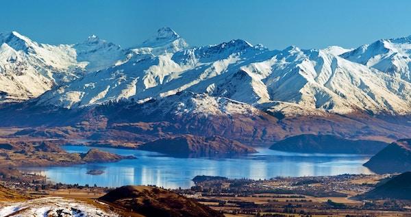 """""""Landskap med snødekt fjellkjede fra Mount Mount, blå Lake Wanaka og Wanaka-township. Klar blå himmel."""""""