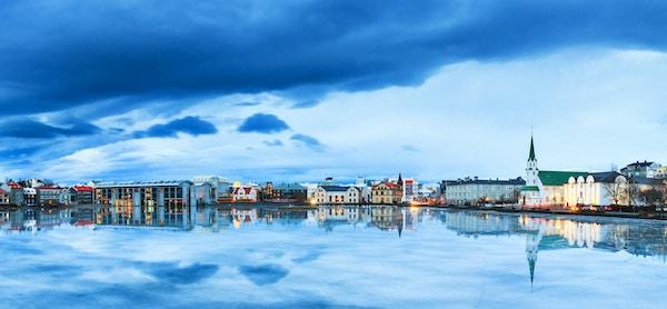 Nydelig panorama av bybildet i Reykjavik, reflektert i Tjornin-sjøen på den blå timen om vinteren