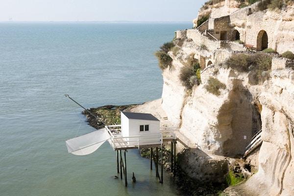 Utsikt fra elvemunningen i Gironde med kalksteinsklippen i landsbyen Meschers sur Gironde og dens troglodytiske hus og tradisjonelle typiske fiskerhytter i tre