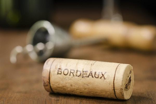 """""""En vinkork fra Bordeaux Frankrike med en korketrekker, vinglass og vinflaske i bakgrunnen."""""""