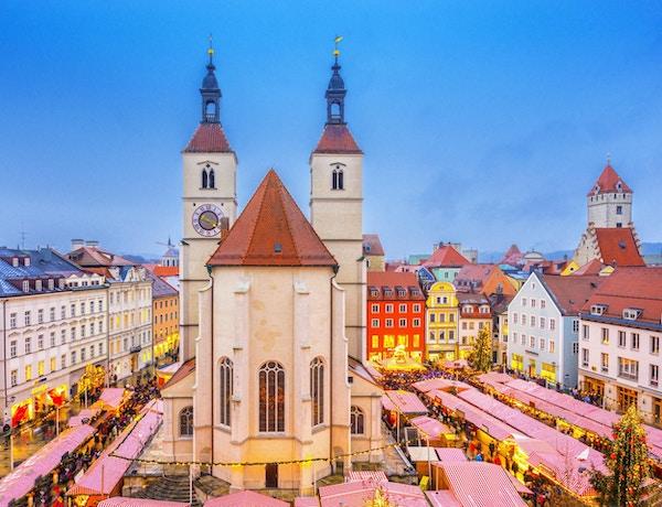 Forhøyet utsikt over Regensburgs julemarked med mat og julepyntboder rundt den 500 år gamle Neupfarr-kirken og vakre byhus.