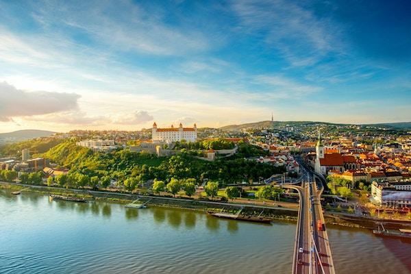 Bratislava flybilde med utsikt over gamlebyen med Saint-Martins katedral, slottshøyden og Donau-elven ved solnedgangen i Slovakia. Vidvinkel med kopieringsplass