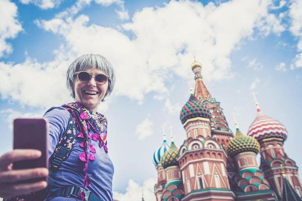 Portrett av en voksen kvinne som tar selfie med Vasilijkatedralen på Den røde plass i Moskva, Russland.