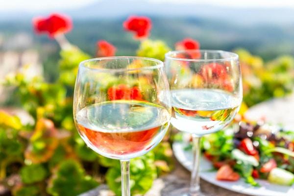 Makro, nærbilde, av, to, glass, hvitvin, og, salat tallerken, inn, hage, med, refleksjon, inn, vann, av, røde, geranium blomster, utenfor, inn, Toscana, italia, sommer
