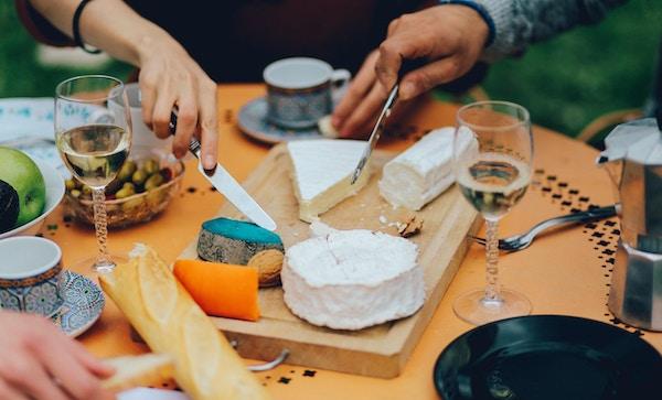 Vintage tonet nærbilde av bordet i hagen til en forstad i Paris, fylt med tradisjonell fransk mat, forskjellige typer ost, vin, hjemmelaget baguettbrød og frukt og grønnsaker. Vennene gleder seg over det fine vårværet, og har en typisk fransk brunsj, med vin, brieost, blåmuggost og baguetter.