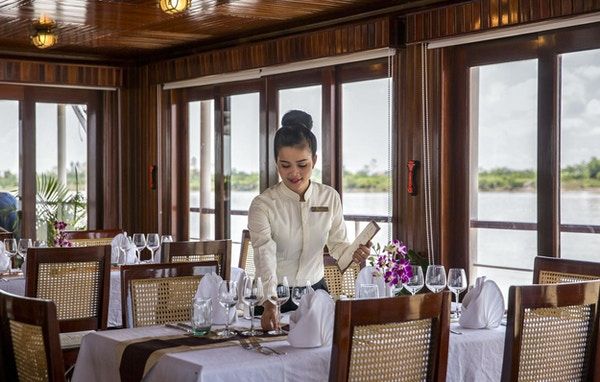 Restaurant på elvecruiseskip med bord, stoler, tallekner, glass, blomster og en dame som dekker bordet. Foto.