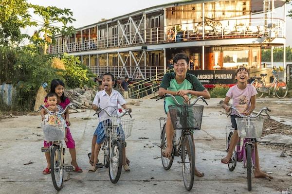 Smilende barn på sykler foran et elvecruiseskip i Vietnam. Foto.