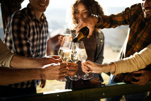 Nærbilde av glade venner som har det gøy mens du drikker champagne på en terrassefest. En av dem skjenker.
