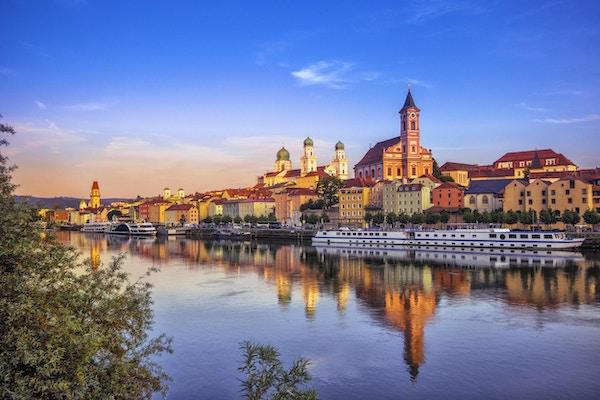 Strandpromenaden og sightseeingbåtene i Passau ved solnedgang.