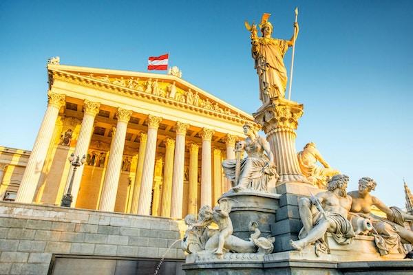 Den østerrikske parlamentsbygningen med statuen Athena i front i Wien ved soloppgangen