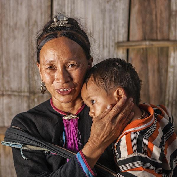 Ung kvinne fra høydestammen som bærer babyen sin i landsbyen i nærheten av Luang Namtha i Laos. Luang Namtha er et populært turistmål i Laos, og en base for turer til de omkringliggende landsbyene i høydestammen.