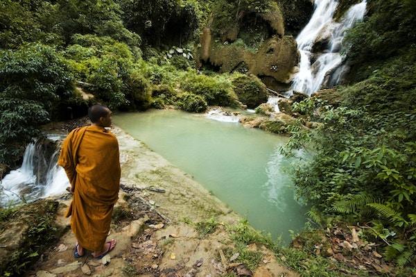 En munk ser på Tat Kuang Si-fossen i Laos